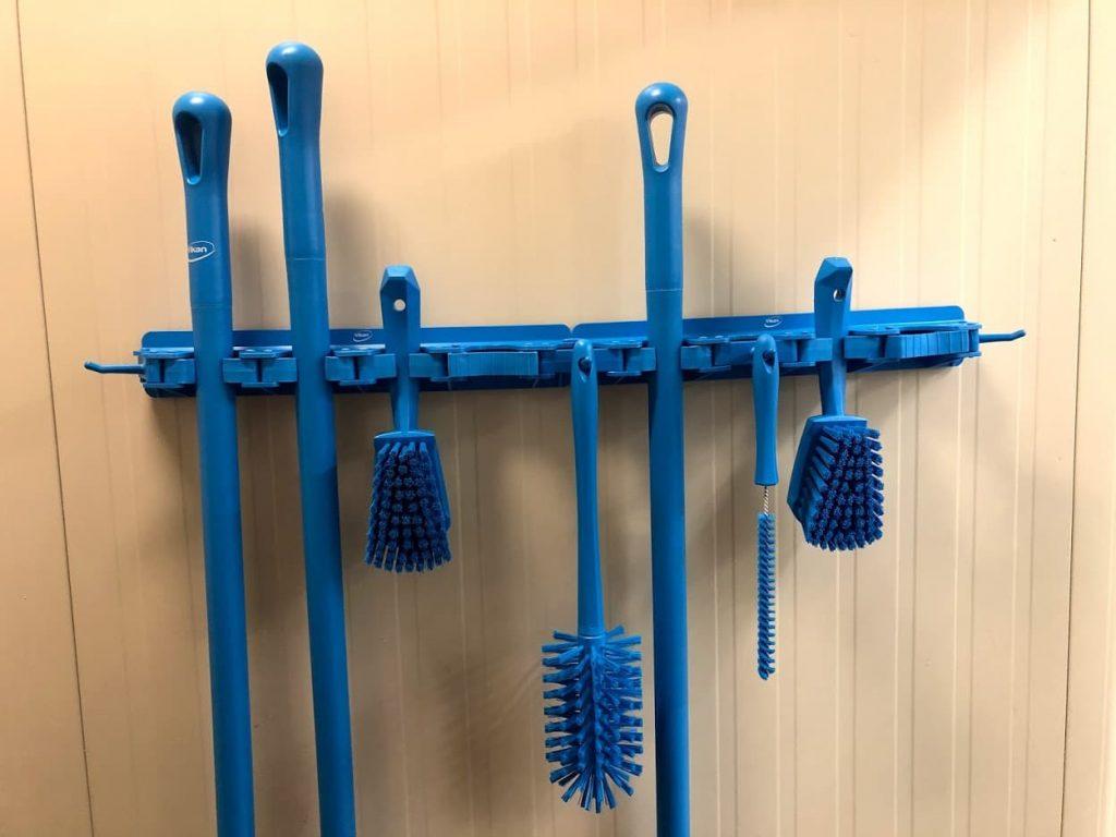 Pribor za čišćenje u plavoj boji na zidnom nosaču