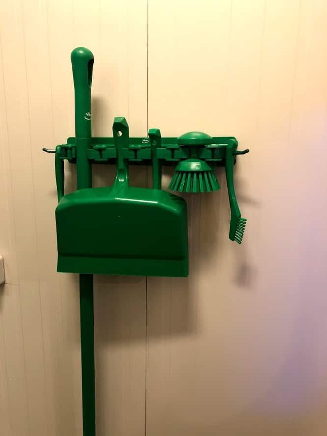 Pribor za čišćenje u zelenoj boji na zidnom nosaču